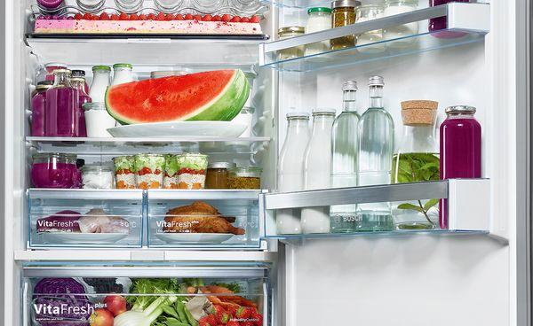 Detaljni pregled iznimno velikog Bosch hladnjaka sa zamrzivačem, punog svježih namirnica poput cijelog pladnja za pečenje, lubenice, voća i povrća.