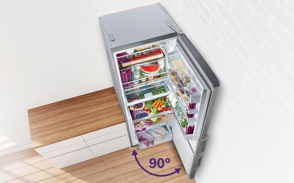 Otvoren veliki samostojeći hladnjak sa zamrzivačem postavljen u kut prostorije. Vrata zamrzivača od 70cm otvorena su pod kutom od 90 stupnjeva, a on je pun svježih namirnica.
